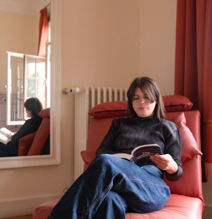 Lesende Stipendiatin in einem roten Ledersofa in ihrem Apartement sitzend