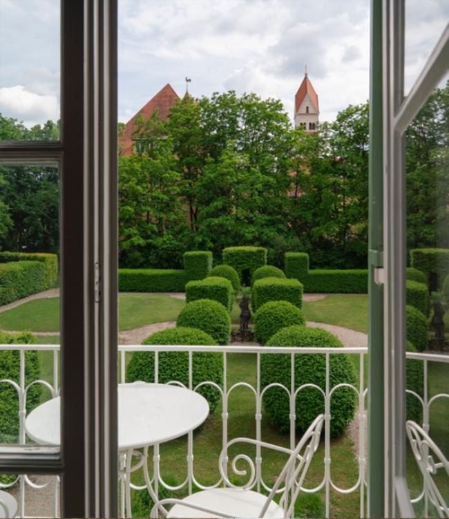 Blick aus einem Fenster in ersten Stock in den Garten mit seinen symmetrisch angeordneten Büschen