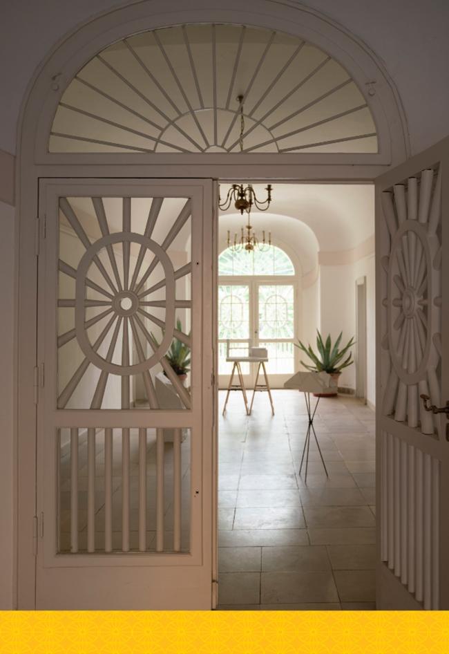 Blick durch eine geöffnete Holztür in einen breiten, hellen Flur des Ebenböckhauses