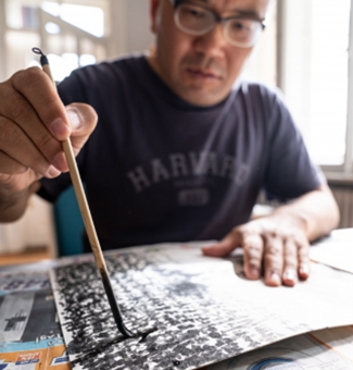 Stipendiat Gwanghee Jeong mit Pinsel malend am Tisch sitzend