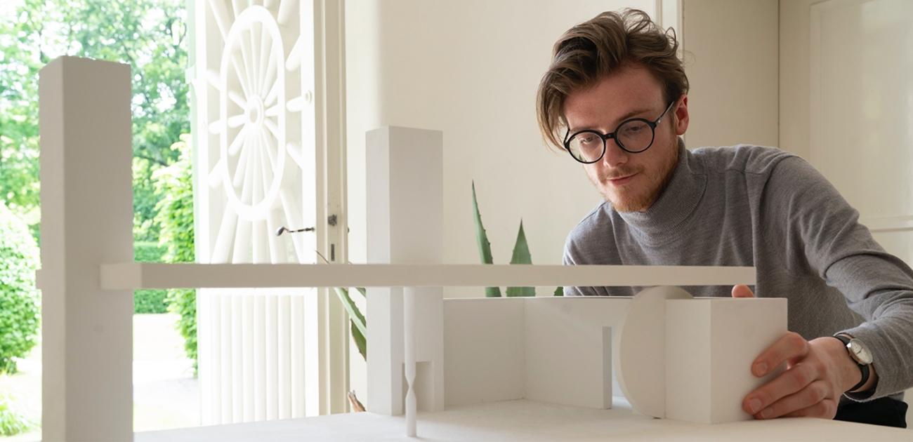Stipendiat Lionel Esche mit einem Architekturmodell vor sich an einem Tisch sitzend